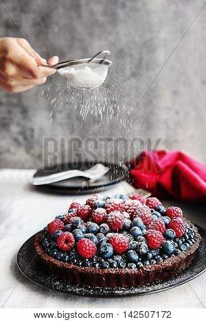 Female hand decorating chocolate tart with berries on black plate