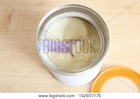 Baby milk formula in can on wooden background