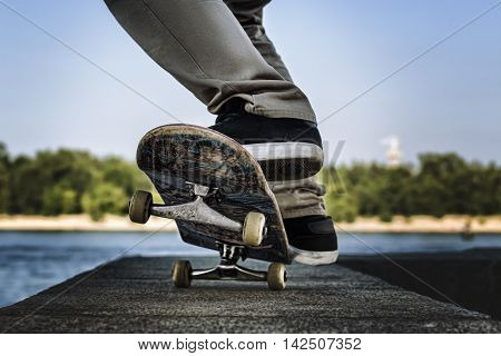 Close up of a skateboarders feet while skating on concrete