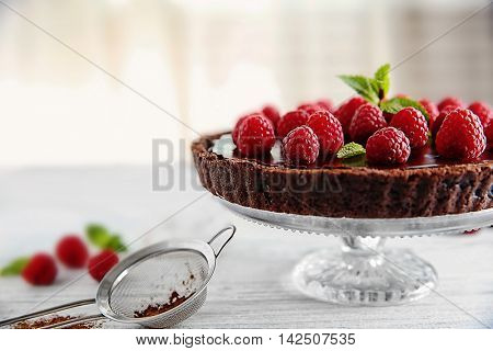 Delicious chocolate tart with raspberry on a white table