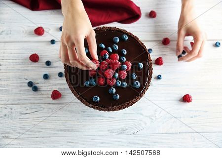 Female hands decorating chocolate tart with berries on wooden background