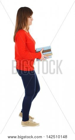 Girl comes with  stack of books. side view. Rear view people collection.  backside view of person.  Isolated over white background.  Girl in red sweater goes to the right with a stack of books.