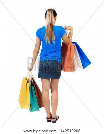 back view of woman with shopping bags. backside view of person.  Rear view people collection. Isolated over white background. girl in a short skirt and a blue shirt holding paper bags.