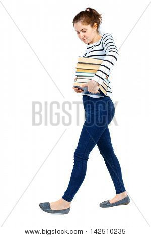 Girl comes with  stack of books. side view. Rear view people collection.  backside view of person.  Isolated over white background. Girl in a striped sweater goes to the side holding a lot of books.