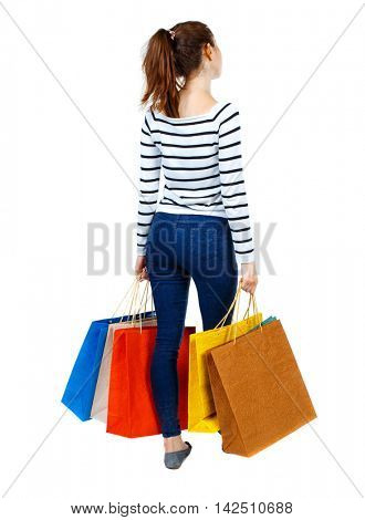 back view of woman with shopping bags. backside view of person.  Rear view people collection. Isolated over white background. Girl in striped sweater holding colorful shopping bags.