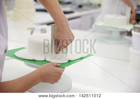 Close Up Of Woman In Bakery Decorating Cake With Royal Icing