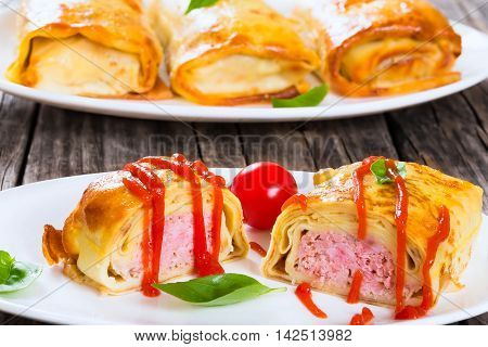 rolled pancakes or crepes stuffed with minced meat poured with tomato sauce on oval dishes served with cherry tomatoes and basil view from above close-up
