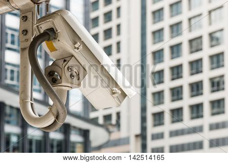Modern cctv camera is hanging neart the office building area.