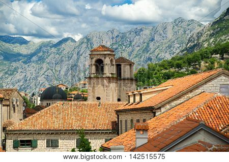 Above red roofs of historic town Kotor in bay of Kotor, with towers of St Tryphon's Cathedral, Montenegro on mountain background