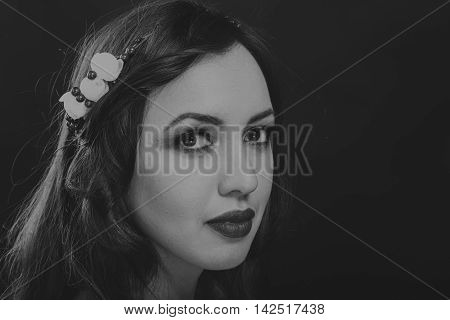 Beautiful mysterious cute brunette on a dark background. Black and white photo Beautiful mysterious brunette.