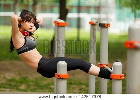 Fit brunette girl doing exercising for her abdominal muscles on the gym bars