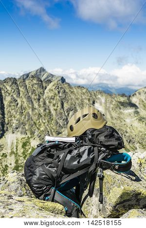 Guide Book, A Helmet And A Backpack With Peaks In The Background.