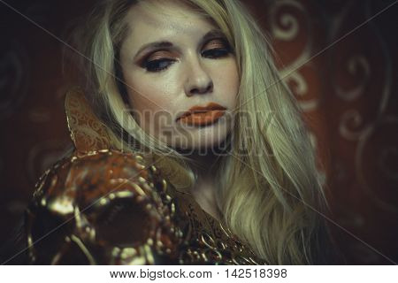 Blonde with long hair and gold with red skull armor and golden threads