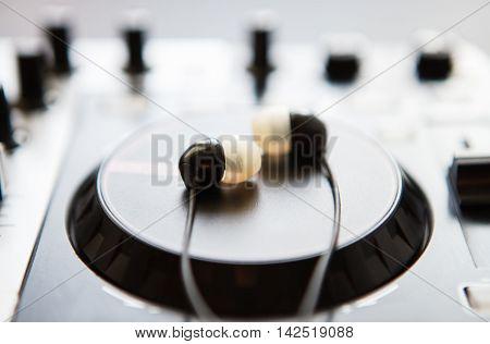In ear headphones lying on DJ midi controller platter. Focus on earpods. Start the party now