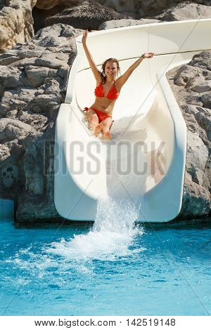 Happy young pretty blond girl sliding on a water slidepipe in aquapark at tropic summer resort. Sunny day attractive woman clean blue water