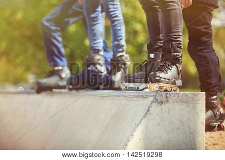 Aggressive Inline Rollerblader Standing On Ramp In Skatepark