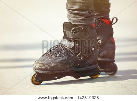 Feet Of Aggressive Inline Rollerblader On Outdoor Skatepark