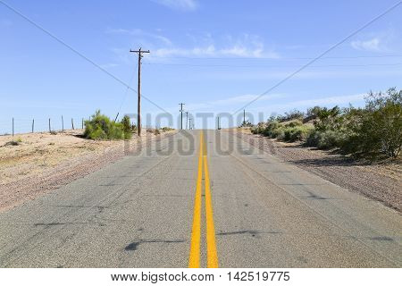 Lonely road in the Sonoran Desert Arizona USA with some shrubs growing on arid ground and overhead power cables to one side.