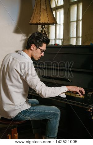 A pianist is playing a piano in a vintage room