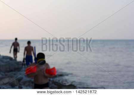 the blurred image of the sea shore with vacationers in the evening