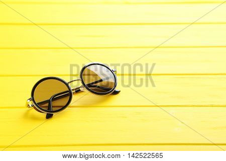 Black Sunglasses On A Yellow Wooden Table