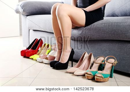 Woman Choosing Shoes On High Heels On Grey Sofa