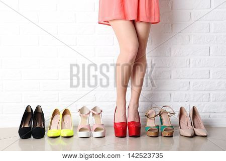 Woman Choosing Shoes On High Heels On Brick Wall Background