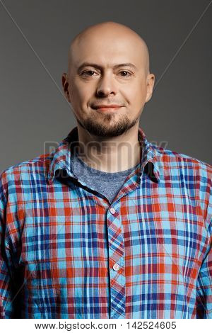 Portrait of cheerful handsome middle-aged man in plaid shirt looking at camera smiling over grey background. Copy space.