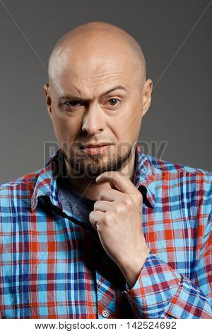 Portrait of confident angry handsome middle-aged man in plaid shirt over grey background. Copy space.