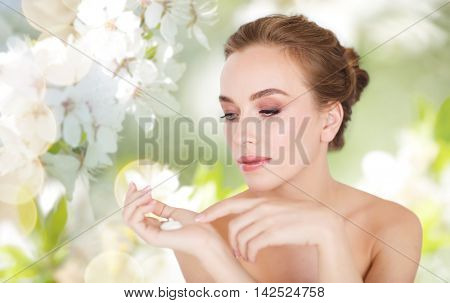 beauty, people, skincare and cosmetics concept - happy young woman with moisturizing cream on hand over natural spring cherry blossom background