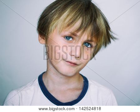 Boy 9 years old in front of a light  background, close-up