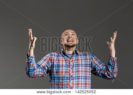 Portrait of handsome middle-aged man screaming up lifting hands in plaid shirt over grey background. Copy space.