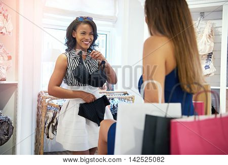 Two young women shopping for clothes in a fashion boutique holding up a bra and panties with a happy smile