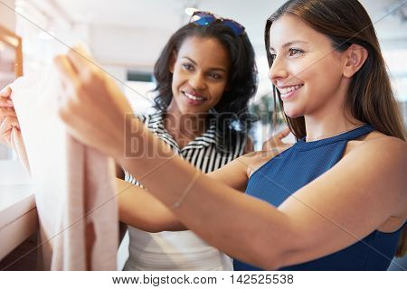Two young female friends shopping for clothes together checking out a top in a boutique with happy smiles