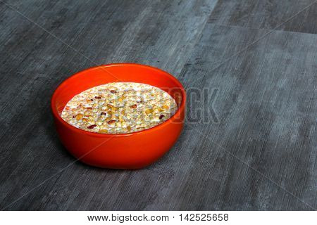 An orange bowl with milk and high protein cereals