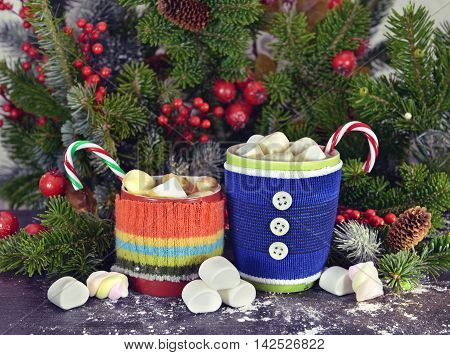 Red and blue warm knitted cups with melted marshmallow, Christmas drink, natural conifer, red berries and sweets. Cozy winter and Christmas time still life with coffee, tea or cocoa