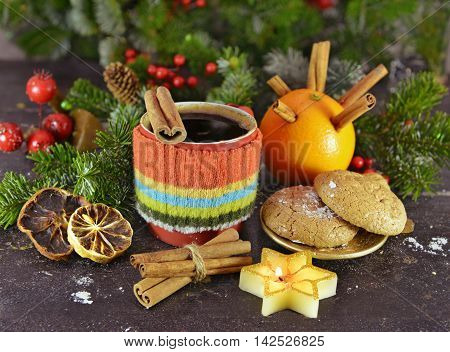 Christmas still life with cozy decorated knitted cup, Christmas drink, candle, natural conifer, red berries, cinnamon and dry oranges. Aroma winter and Christmas time still life with coffee beverage
