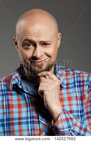Portrait of handsome cheerful middle-aged man in plaid shirt playfuly winking at camera over grey background. Copy space.