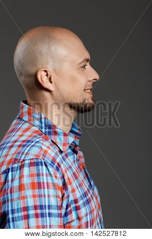 Profile portrait of confident handsome middle-aged man in plaid shirt over grey background. Copy space.