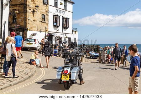 aROBIN HOODS BAY, ENGLAND - AUGUST 12: Motorbikers arrive outside The Bay Hotel. In Robin Hoods Bay, North Yorkshire, England. On 12th August 2016.