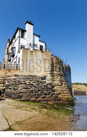 ROBIN HOODS BAY, ENGLAND - AUGUST 12: The Bay Hotel at the edge of the beach. In Robin Hoods Bay, North Yorkshire, England. On 12th August 2016.