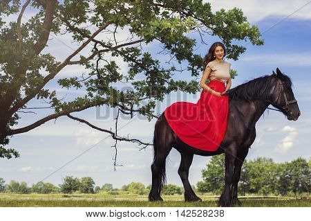 Beautiful woman with trendy make-up and in long red dress sitting on a black horse under a big tree. Horse riding concept.