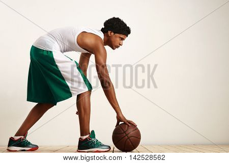 Back Shot Photo Of Basketball Player Holding The Ball At His Side On Grunge Background