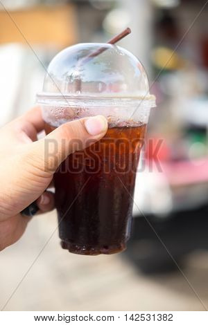 Iced Americano black coffee in takeaway cup in hand