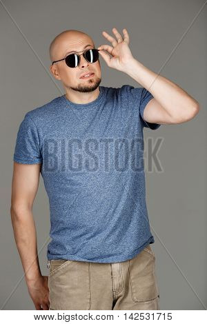 Portrait of confident handsome middle-aged man in grey shirt and sunglasses posing over dark background. Copy space.