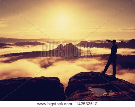 Tall Hiker In Black Enjoing Orange Sunrise On View Point. Heavy Mist Bellow In Valley.