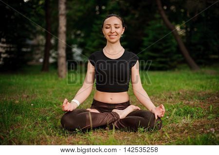 young girl meditating in the forest nature