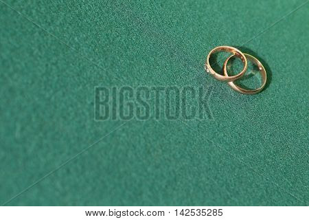 Background with two golden wedding rings on green cloth