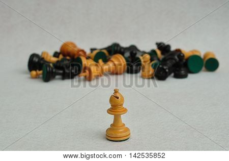 A white bishop in focus with the rest of the chess pieces out of focus on a white background