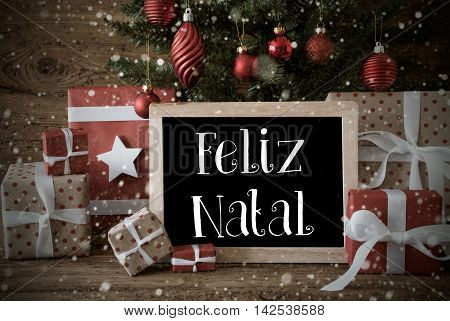 Nostalgic Christmas Card For Seasons Greetings. Christmas Tree With Balls And Snowflakes. Gifts In The Front Of Wooden Background. Chalkboard With Portuguese Text Feliz Natal Means Merry Christmas